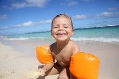 Μικρό κορίτσι με armbands που απολαμβάνει στην παραλία Στοκ Εικόνες