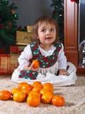 Μικρό κορίτσι με tangerines στο δωμάτιο με το decoratio Χριστουγέννων Στοκ Εικόνες