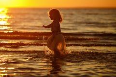 Μικρό κορίτσι μικρών κοριτσιών σε μια φούστα και ένα ριγωτό thro τρεξιμάτων πουλόβερ Στοκ Φωτογραφίες