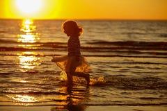 Μικρό κορίτσι μικρών κοριτσιών σε μια φούστα και ένα ριγωτό thro τρεξιμάτων πουλόβερ Στοκ Εικόνα