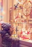 Μικρό κορίτσι μπροστά από το παράθυρο ενός καταστήματος, πλήρες των τυλιγμένων δώρων στοκ φωτογραφία