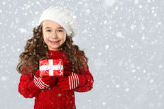 Μικρό κορίτσι μόδας με το δώρο Χριστουγέννων, στο υπόβαθρο χιονιού Στοκ Φωτογραφία