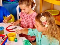Μικρό κορίτσι ομάδας με τη ζωγραφική βουρτσών στον παιδικό σταθμό Στοκ Φωτογραφίες
