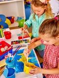 Μικρό κορίτσι ομάδας με τη ζωγραφική βουρτσών στον παιδικό σταθμό Στοκ εικόνες με δικαίωμα ελεύθερης χρήσης