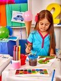 Μικρό κορίτσι ομάδας με τη ζωγραφική βουρτσών στον παιδικό σταθμό Στοκ Εικόνα