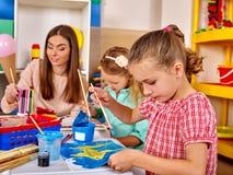 Μικρό κορίτσι ομάδας με τη ζωγραφική βουρτσών στον παιδικό σταθμό Στοκ φωτογραφία με δικαίωμα ελεύθερης χρήσης