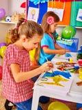 Μικρό κορίτσι ομάδας με τη ζωγραφική βουρτσών στον παιδικό σταθμό Στοκ Φωτογραφία