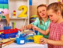 Μικρό κορίτσι ομάδας με τη ζωγραφική βουρτσών στο δημοτικό σχολείο Στοκ Εικόνες
