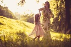 Μικρό κορίτσι ομορφιάς με τη μητέρα της που παίζει στη φύση Στοκ Φωτογραφία
