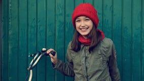 Μικρό κορίτσι παιδιών στο κόκκινο καπέλο με το ποδήλατο δίπλα στον μπλε ναυτικό τοίχο που κάνει τα πρόσωπα απόθεμα βίντεο