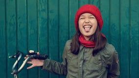 Μικρό κορίτσι παιδιών στο κόκκινο καπέλο με το ποδήλατο δίπλα στον μπλε ναυτικό τοίχο που κάνει τα πρόσωπα φιλμ μικρού μήκους