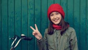 Μικρό κορίτσι παιδιών στο κόκκινο καπέλο με το ποδήλατο δίπλα στον μπλε ναυτικό τοίχο που παρουσιάζει ειρήνη με τα δάχτυλα φιλμ μικρού μήκους