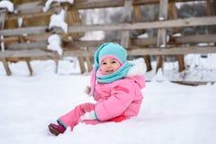 Μικρό κορίτσι περιπάτους ενός στους ρόδινους jumpsuit σε ένα χιονώδες χειμερινό πάρκο στοκ φωτογραφία