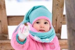 Μικρό κορίτσι περιπάτους ενός στους ρόδινους jumpsuit σε ένα χιονώδες χειμερινό πάρκο στοκ εικόνες