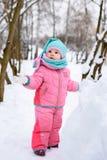 Μικρό κορίτσι περιπάτους ενός στους ρόδινους jumpsuit σε ένα χιονώδες χειμερινό πάρκο στοκ φωτογραφίες με δικαίωμα ελεύθερης χρήσης