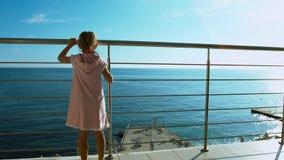 Μικρό κορίτσι που έρχεται στο κιγκλίδωμα και που εξετάζει τη θάλασσα Στοκ Εικόνα