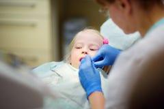 Μικρό κορίτσι που έχει τα δόντια της εξετασμένων από τον οδοντίατρο Στοκ Φωτογραφίες