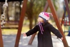 Μικρό κορίτσι που έχει τη διασκέδαση στην υπαίθρια παιδική χαρά την ημέρα άνοιξης ή φθινοπώρου Στοκ Φωτογραφία
