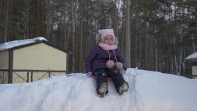 Μικρό κορίτσι που έχει τη διασκέδαση στο έλκηθρο στο χιονώδη λόφο απόθεμα βίντεο