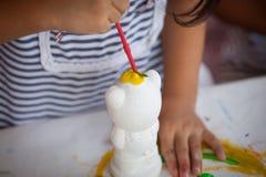 Μικρό κορίτσι που έχει τη διασκέδαση για να χρωματίσει στην κούκλα στόκων Στοκ Εικόνα