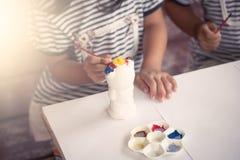 Μικρό κορίτσι που έχει τη διασκέδαση για να χρωματίσει στην κούκλα στόκων Στοκ Εικόνες
