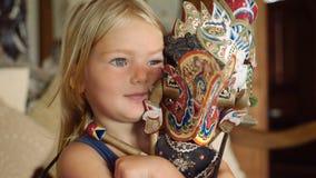 Μικρό κορίτσι που αγκαλιάζει μια από το Μπαλί κούκλα στη βαθιά σκέψη απόθεμα βίντεο