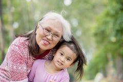 Μικρό κορίτσι που αγκαλιάζεται ευτυχές από τη γιαγιά της στοκ εικόνα με δικαίωμα ελεύθερης χρήσης