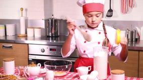 Μικρό κορίτσι που ανακατώνεται σε μια βάση κύπελλων για τη ζύμη φιλμ μικρού μήκους