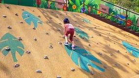 Μικρό κορίτσι που αναρριχείται επάνω σε έναν τοίχο βράχου στην παιδική χαρά απόθεμα βίντεο