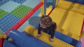 Μικρό κορίτσι που αναρριχείται στα σκαλοπάτια στο κέντρο παιχνιδιού των παιδιών απόθεμα βίντεο