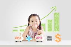 Μικρό κορίτσι που βάζει τα χρήματα σε μια piggy τράπεζα με ένα νέο έτος 2015 Στοκ Εικόνα