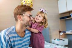 Μικρό κορίτσι που βάζει τη χρυσή κορώνα στο κεφάλι του μπαμπά στοκ εικόνες