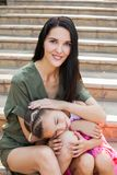 Μικρό κορίτσι που βάζει το κεφάλι στα γόνατα μητέρων ` s στα σκαλοπάτια Στοκ φωτογραφία με δικαίωμα ελεύθερης χρήσης