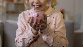 Μικρό κορίτσι που βάζει το νόμισμα στη piggy τράπεζα, που κερδίζει χρήματα για το όνειρο παιδιών, κινηματογράφηση σε πρώτο πλάνο φιλμ μικρού μήκους