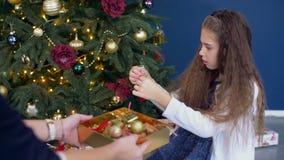 Μικρό κορίτσι που βοηθά διακοσμώντας το χριστουγεννιάτικο δέντρο απόθεμα βίντεο