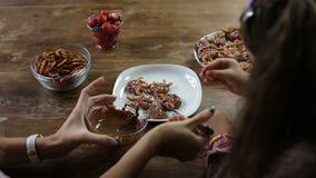 Μικρό κορίτσι που βοηθά τη μητέρα για να διακοσμήσει το μπισκότο Χριστουγέννων απόθεμα βίντεο