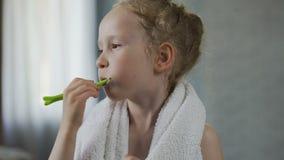 Μικρό κορίτσι που βουρτσίζει τα δόντια της επιμελώς, οδοντική υγιεινή, τελετουργικό πρωινού φιλμ μικρού μήκους