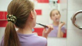 Μικρό κορίτσι που βουρτσίζει τα δόντια της στο λουτρό απόθεμα βίντεο