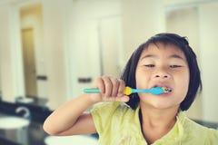 Μικρό κορίτσι που βουρτσίζει τα δόντια της που απομονώνονται στην τουαλέτα Στοκ Φωτογραφία