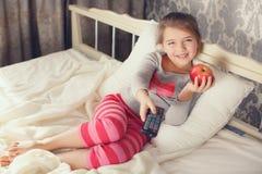 Μικρό κορίτσι που βρίσκεται στο κρεβάτι με μια TV τηλεχειρισμού Στοκ Εικόνα