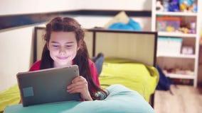Μικρό κορίτσι που βρίσκεται στο κρεβάτι που παίζει την ψηφιακή ταμπλέτα μικρό κορίτσι που παίζει την ψηφιακή συνεδρίαση μικρών κο απόθεμα βίντεο