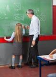 Μικρό κορίτσι που γράφει εν πλω με το δάσκαλο στοκ φωτογραφία με δικαίωμα ελεύθερης χρήσης