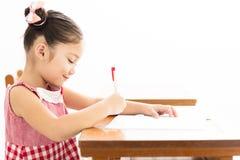 μικρό κορίτσι που γράφει στο γραφείο στην τάξη στοκ φωτογραφία με δικαίωμα ελεύθερης χρήσης