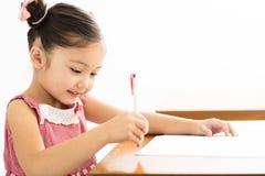 μικρό κορίτσι που γράφει στο γραφείο στην τάξη στοκ εικόνες