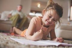 Μικρό κορίτσι που γράφει στο σπίτι Στοκ εικόνες με δικαίωμα ελεύθερης χρήσης