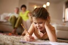 Μικρό κορίτσι που γράφει στο σπίτι Στοκ εικόνα με δικαίωμα ελεύθερης χρήσης
