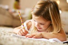 Μικρό κορίτσι που γράφει στο σπίτι Στοκ Φωτογραφία