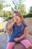Μικρό κορίτσι που δαγκώνει το πορτοκαλί γλειφιτζούρι πάγου στο πάρκο στοκ φωτογραφία με δικαίωμα ελεύθερης χρήσης