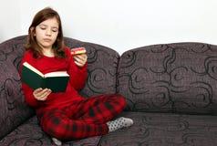 Μικρό κορίτσι που διαβάζει ένα βιβλίο και που τρώει doughnut Στοκ Εικόνες