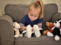 Μικρό κορίτσι που διαβάζει μια συνεδρίαση βιβλίων σε μια καρέκλα στοκ φωτογραφία με δικαίωμα ελεύθερης χρήσης